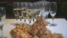 Glasses with champagne on party table. Close-up stock footage