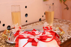 Glasses of a champagne and pillow with wedding rings Stock Photo