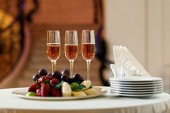 Glasses of champagne and a plate of fruit on the table. In the restaurant. buffet table stock images