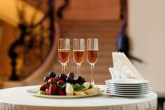 Glasses of champagne and a plate of fruit on the table. In the restaurant. buffet table royalty free stock image