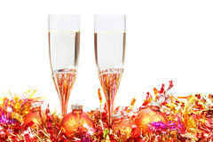 Glasses of champagne and red and orange Xmas balls Royalty Free Stock Images