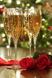Glasses of champagne and red roses Stock Photos