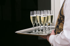 Glasses with champagne on tray in hands of waiter Royalty Free Stock Image
