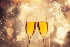 Glasses of champagne on sparkling holiday background with fireworks. On the sky stock image