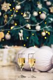 Glasses with champagne stand on floor against background of Christmas tree. stock image