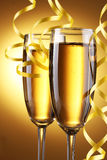 Glasses of champagne and streamer Stock Images