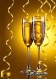 Glasses of champagne and streamer. On yellow background Royalty Free Stock Photos