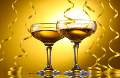 Glasses of champagne and streamer. On yellow background Stock Photo