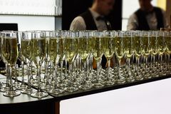Glasses of champagne are on the table. In the background are two waiter stock photo