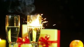 Glasses with champagne on the table and fireworks from Bengal candle stock video