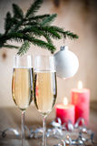 Glasses of champagne under decorated christmas tree branch Royalty Free Stock Images