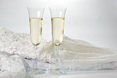 Glasses with champagne and wedding dress on a white background.  Royalty Free Stock Images