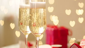 Glasses with champagne, wedding rings and hearted bokeh on wedding day. Panorama of filling glass with champagne, gold wedding rings and holiday decoration with stock video