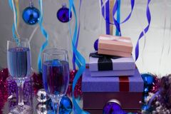 glasses with champagne on a wooden table with Christmas red balls, a glossy ribbon with a sprig of spruce on the backg Royalty Free Stock Photography