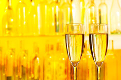 Glasses of champagne on a yellow bar background Stock Photo