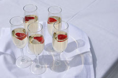 Glasses with champain and strawberries. On white tray Stock Images