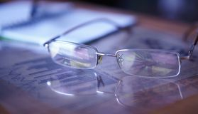 Glasses with charts. Pie chart on reflection. Royalty Free Stock Photography