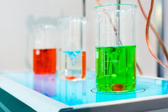 Glasses with chemical liquids are on a magnetic stirrer. Royalty Free Stock Photography