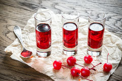 Glasses of cherry brandy with cocktail cherries Stock Photos