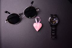 Glasses and clock in the style of steampunk with a pink heart in the center on a black background. Top white view mens accessories wheels flat office work lay royalty free stock photography