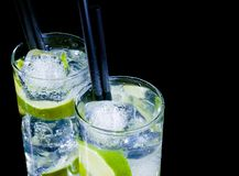 Glasses with cocktail and ice with lime slice on black background with space for text royalty free stock image
