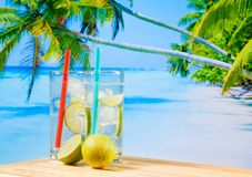 Glasses of cocktail with lime slice on blur beach and palm Stock Images