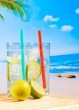 Glasses of cocktail with lime slice on blur beach Royalty Free Stock Image