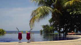 Glasses with a cocktail near the pool. Two glasses cocktails on background of pool, sea, palm tree. Cocktails with dragonfruit near the pool. Summer drinks stock video footage