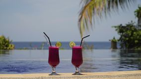 Glasses with a cocktail near the pool. Two glasses cocktails on background of pool, sea, palm tree. Cocktails with dragonfruit near the pool. Summer drinks stock footage