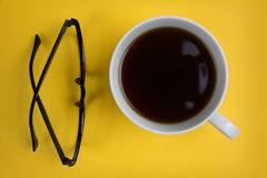 Glasses and coffee cup on bright yellow background. Overhead shot of coffee cup and glasses Royalty Free Stock Image