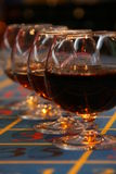 Glasses of Cognac Poker Table. Row of balloon brandy glasses or snifters filled with cognac on a blue casino roulette gambling table royalty free stock image