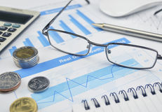 Glasses, coin and pen on financial chart and graph, investment c Stock Images