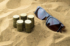 Glasses and coins in the sand Royalty Free Stock Photo