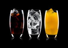 Glasses of cola and orange soda drink and lemonade. Sparkling water on black background with ice cubes Royalty Free Stock Photo