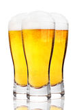 Glasses of cold beer with foam and froth on white. Background stock images
