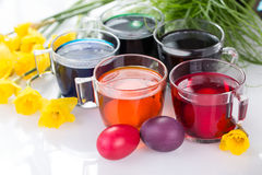 Glasses with colored food colors for traditional Easter egg coloring and Easter eggs and daffodils. Egg dyeing, painting Easter eggs with food colors Stock Photo