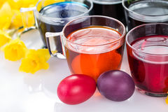 Glasses with colored food colors for traditional Easter egg coloring and Easter eggs and daffodils. Egg dyeing, painting Easter eggs with food colors Royalty Free Stock Photos