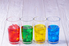 Glasses with colored water and ice. On a white wooden fonne stock images