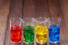 Glasses with colored water and ice. On a wooden fonne Stock Photography