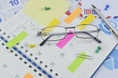 Glasses with colorful sticky notes and pen on diary page Stock Photos
