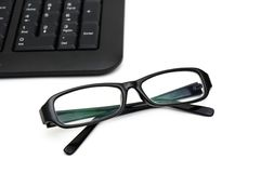 Glasses on computer keyboard Stock Photo
