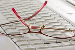 Glasses on the computer keyboard Stock Image