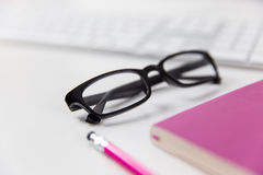Glasses, computer keyboard and notebook on office desk. Modern office worksapce with computer and glasses Stock Photo