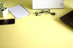 Glasses, computer and pen notebooks placed on a yellow background. Working concept royalty free stock photo