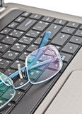 Glasses on computer's keyboard Royalty Free Stock Photos