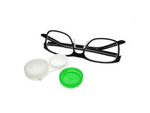 Glasses and contact lenses container on white background Stock Images