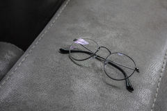 A glasses on the corner of leather sofa Royalty Free Stock Photography