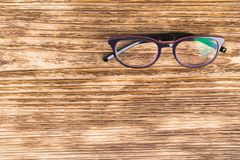 Glasses for correcting vision lie on a dark wooden background stock photography