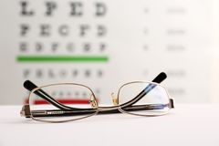 Glasses with corrective lenses. On table against eye chart royalty free stock images