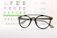Glasses with corrective lenses. On table against eye chart stock photography